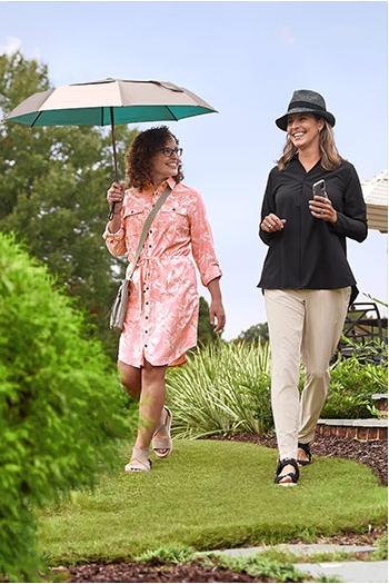 Womens Travel - 2 women walking outside with umbrella